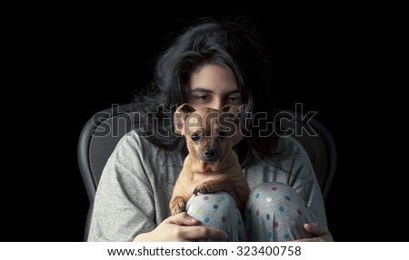 Low key shot of latina teenage girl holding her chihuahua dog (its ears curled back to create a funny appearance)