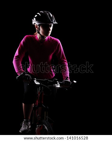 Low key silhouette of a girl cyclist riding her bicycle looking to the copy space area - stock photo