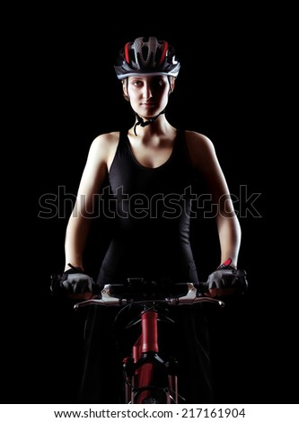 low key silhouette of a girl cyclist  with her bicycle on black background - stock photo