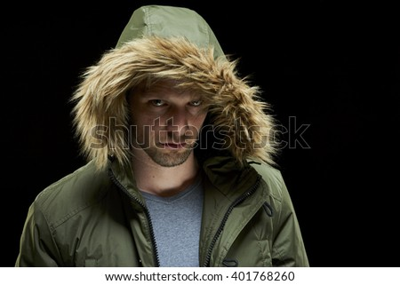 Low key studio portrait of suspicious young adult caucasian model wearing winter coat with hood on. - stock photo