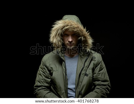 Low key studio portrait of suspicious young adult caucasian model wearing winter coat with hood on. Isolated on black. - stock photo