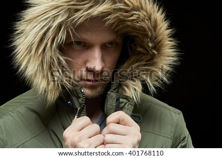 Low key studio portrait of young adult caucasian model wearing winter coat with hood on. Isolated on black. - stock photo