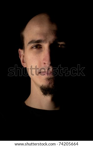Low key studio portrait of young handsome man over black background