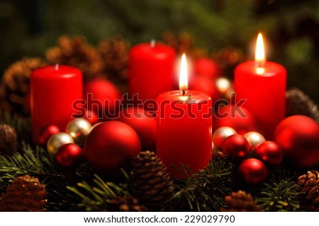 Low-key studio shot of a nice advent wreath with baubles and two burning red candles - stock photo