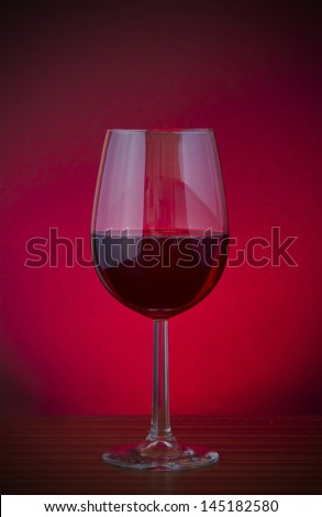 Low key vignette image of red wine in a glass
