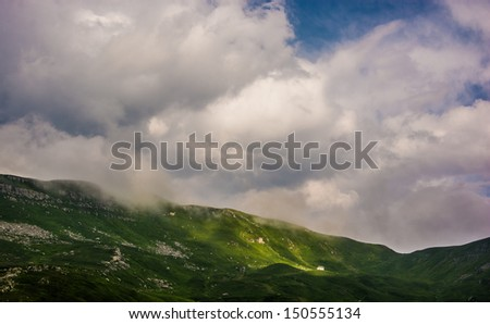 Low level clouds in a mountain landscape with isolated hut