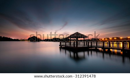 Low light long exposure scenery of a lake with wooden observation jetty in blue hour, with motion blur effects on surface of water and sky.