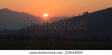 low light sunset landscape with car traveling in bulgarian country road  - stock photo