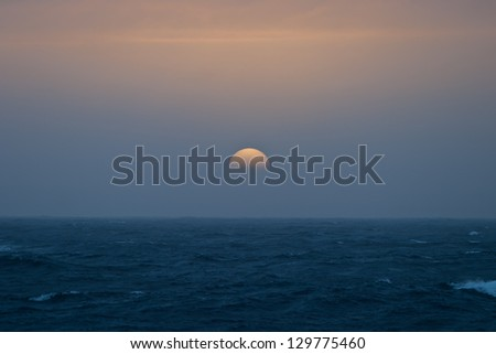 Low on the horizon, the sun shows as a beautiful ball of color.  Antarctica has some of the most beautiful sunrises and sunsets on Earth. - stock photo