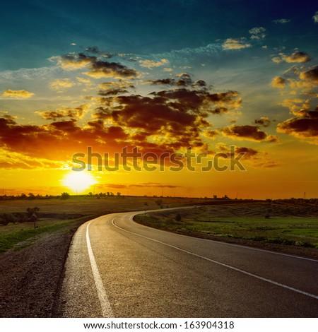 low orange sun over asphalt road - stock photo