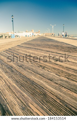 Low perspective of old wood boardwalk on New Jersey shore - stock photo