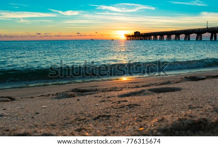 low perspective of sun rising  behind the pier and waves crashing on the sand