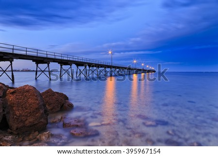 low point view of long wooden jetty and coastal rocks in Ceduna town bay when transparent water shows shallow seabed at sunrise. - stock photo