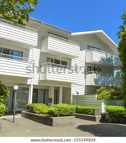 Low-rise apartment building in suburb of Vancouver, Canada. Apartment building on a sunny day with blue sky background. - stock photo