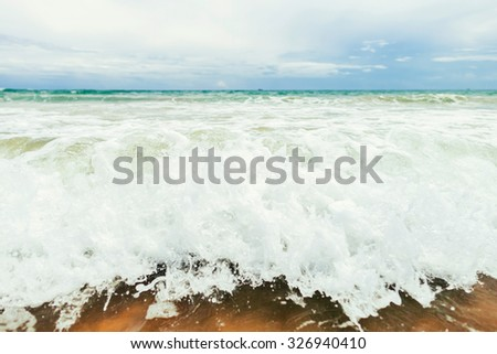 low sea water with waves and  foam in tropics