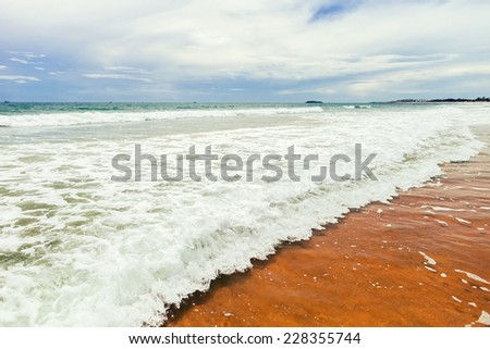 low sea waves with transparent water and foam at the paradise island / low water with sea waves and foam