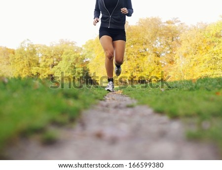 Low section image of female athlete running in park. Young woman jogging and exercising for good health.