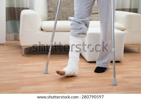 Low Section Of A Disabled Man Using Crutches For Walking