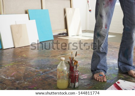 Low section of a male artist standing by paint brushes and paint thinner in studio - stock photo