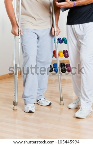 Low section of a man holding crutches standing by trainer