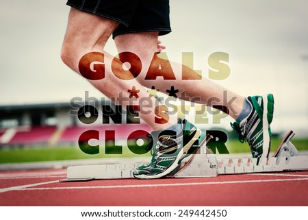 Low section of a man ready to race on running track against goals one step closer - stock photo
