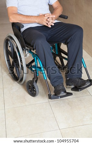 Low section of a senior man sitting in a wheelchair at hospital corridor - stock photo