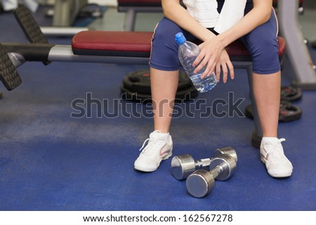 Low section of a tired and thoughtful young woman sitting in the gym - stock photo