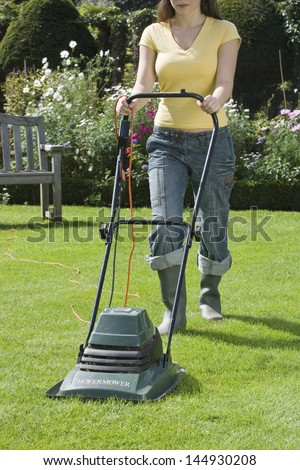Low section of a woman mowing the lawn with electric mower