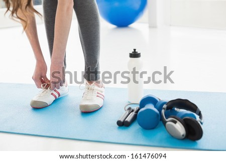 Low section of a woman tying shoes with sporty equipment on floor in fitness center - stock photo