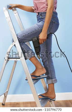 Low section of a woman with driller climbing ladder - stock photo