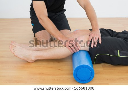 Low section of a young man getting his knee examined by a physical therapist - stock photo