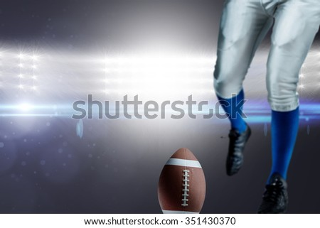 Low section of American football player kicking ball against spotlights - stock photo