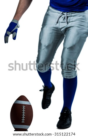 Low section of American football player kicking ball over white background - stock photo