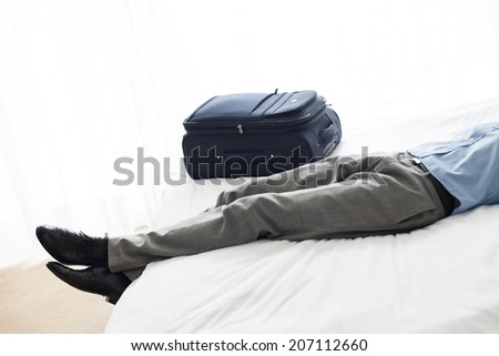 Low section of businessman sleeping beside luggage in hotel room - stock photo