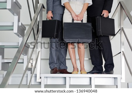Low section of businesspeople with briefcases standing on steps at office - stock photo