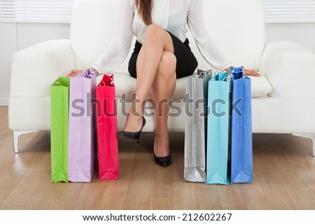 Low section of businesswoman sitting on sofa with multicolored shopping bags on floor at home