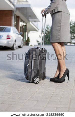 Low section of businesswoman standing with suitcase on driveway - stock photo