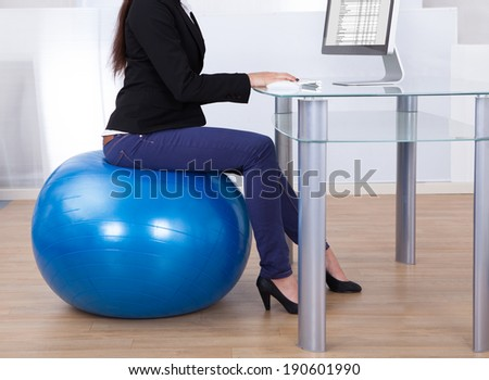 Low section of businesswoman using computer while sitting on pilates ball in office - stock photo