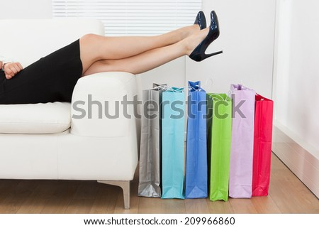 Low section of businesswoman with legs over multicolored shopping bags at home - stock photo