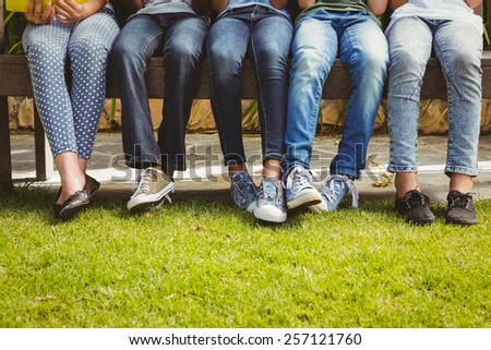 Low section of children sitting in row at park - stock photo