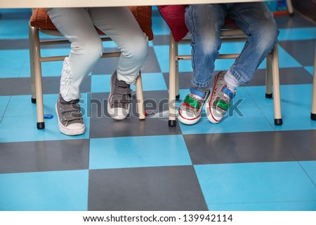 Low section of children sitting on chair in classroom - stock photo