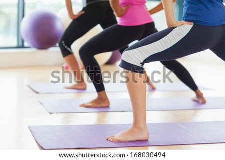 Low section of class and instructor doing stretching pilate exercises in fitness studio - stock photo
