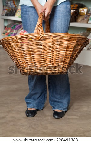 Low section of female customer carrying shopping basket in grocery store - stock photo