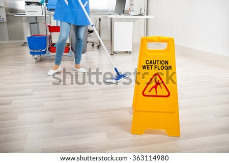 Low section of female janitor mopping floor by yellow wet caution sign in office - stock photo