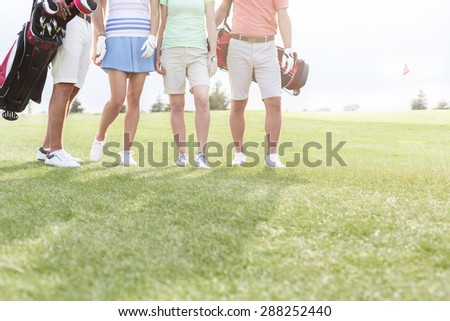 Low section of friends standing at golf course - stock photo