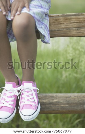 Low section of girl wearing pink shoes