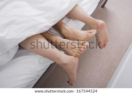 Low section of intimate couple in bed - stock photo
