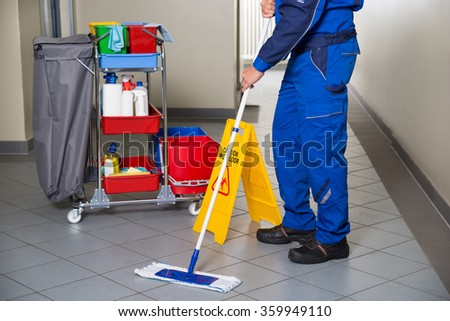 Low section of male janitor with broom cleaning office corridor - stock photo