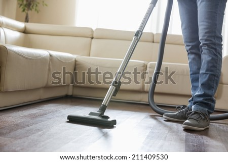 Low section of man cleaning hardwood floor with vacuum cleaner - stock photo