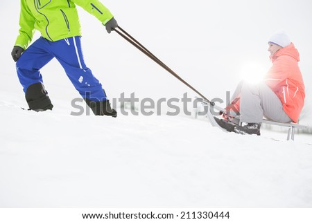 Low section of man giving sled ride to woman in snow - stock photo